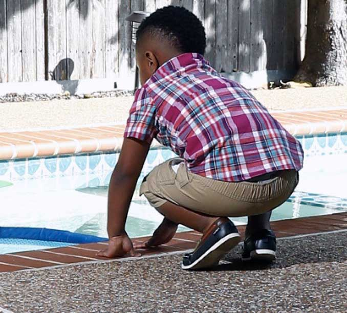 Child leaning over pool