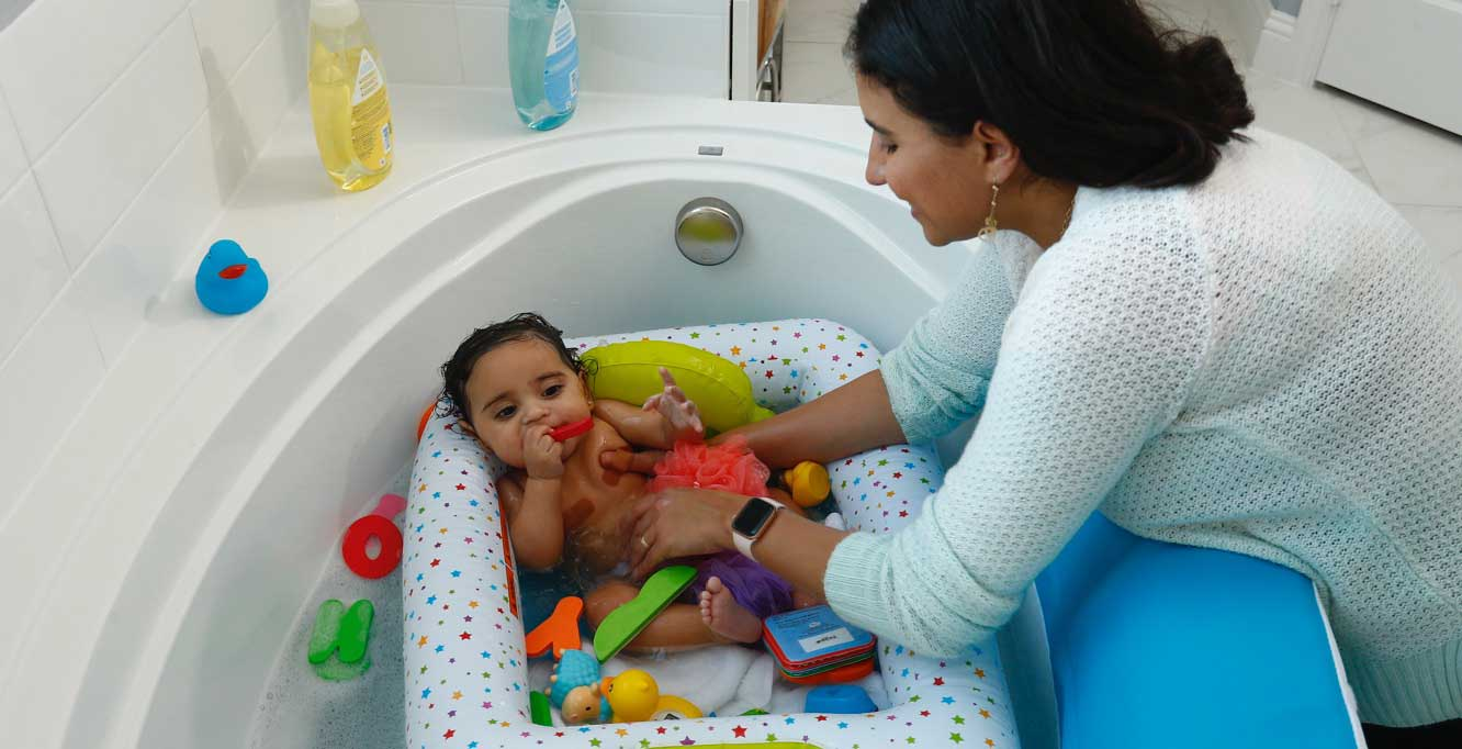 Mother smiling with daughter in bathtub