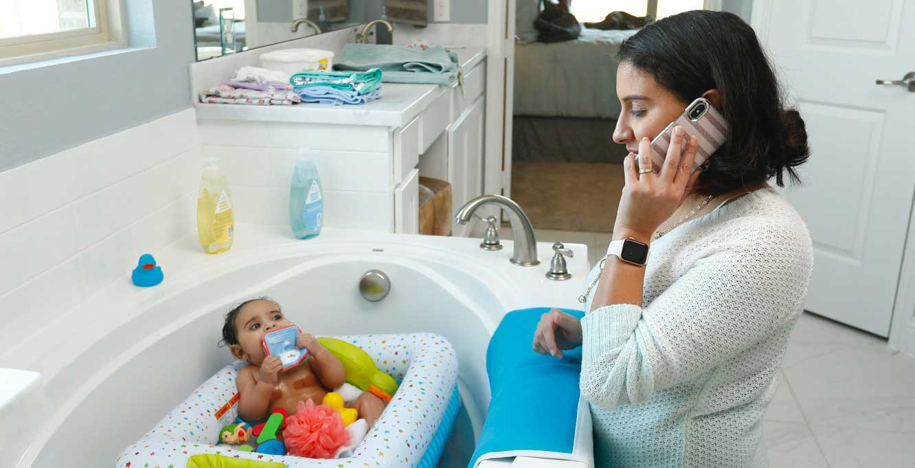 Mother on phone during bath time
